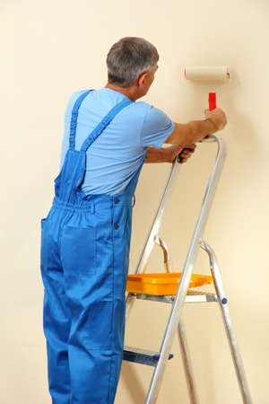 Male painter paints wall in room close-up photo