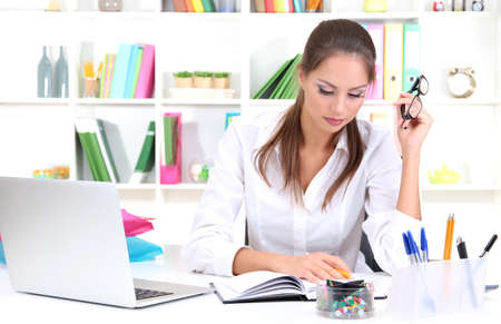 Thoughtful business woman with notebook in office Stock Photo - 17051670
