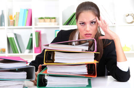 tired business woman with documents in her workplace photo
