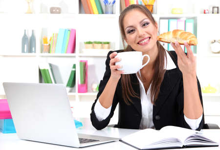 business woman has snack on workplace photo