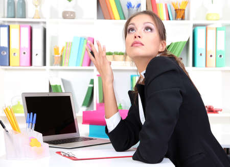 Thoughtful business woman with documents and notebook in office Stock Photo - 17051689