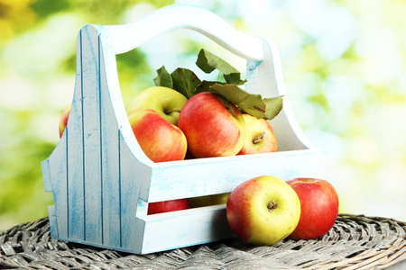 juicy apples with leaves in wooden basket, on green background Stock Photo - 16605008