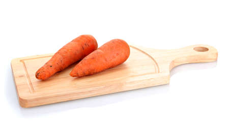 carrots on wooden cutting board isolated on white photo