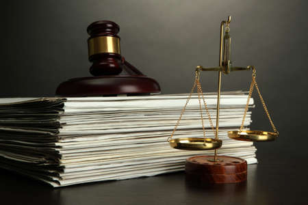 defendant: Golden scales of justice, gavel and books on grey background Stock Photo