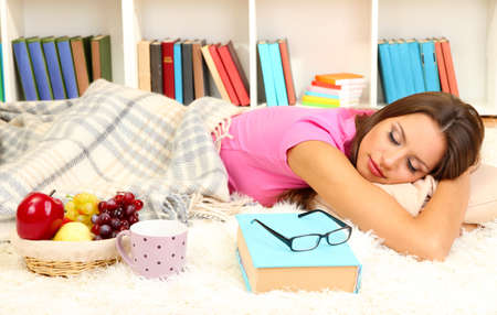 Young female asleep while reading book on floor Stock Photo - 17051743