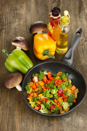 Sliced fresh vegetables in pan with spices and ingredients on wooden table photo