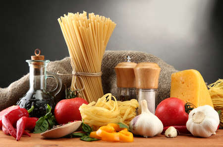 dry food: Pasta spaghetti, vegetables and spices, on wooden table, on grey background