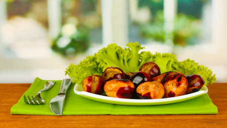 roasted chestnuts with lettuce in the plate on wooden table close-up photo