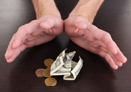 economise: Money, which take hands on wooden table background
