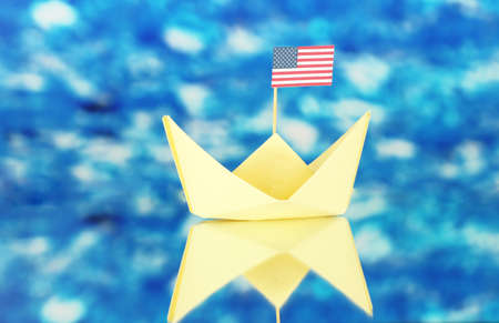 Ship with the American flag, on blue background. Columbus Day.