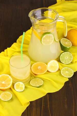 Citrus lemonade in glass and pitcher of citrus around on yellow fabric on wooden table close-up photo