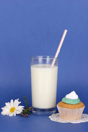 Glass of fresh new milk with cake on blue background photo