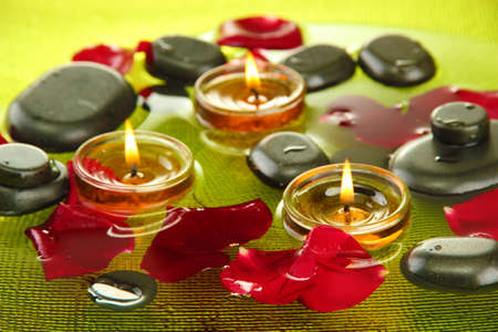 spa stones with rose petals and candles in water on plate photo