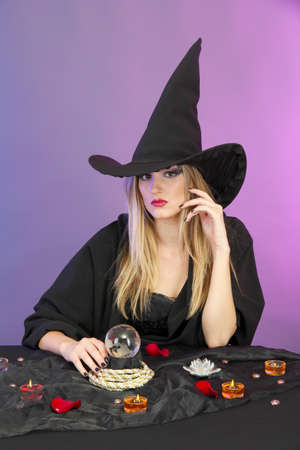 Witch with crystal ball. Fortune telling. On color background photo