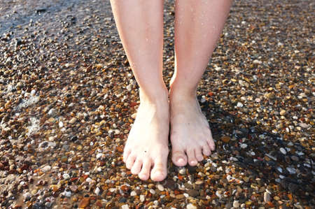 legs walking on beach stones close-up photo
