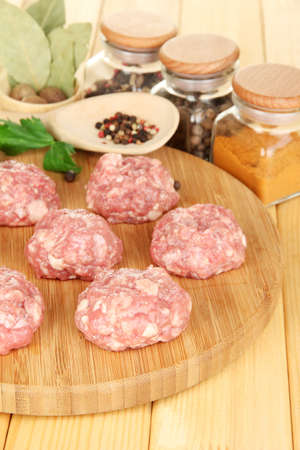 Raw meatballs with spices on wooden table Stock Photo - 16619765