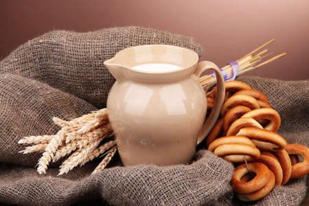 boublik: jar of milk, tasty bagels and spikelets on wooden table, on brown background Stock Photo