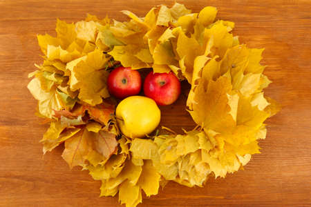 Autumnal composition with yellow leaves, apples on wooden background Stock Photo - 16619714
