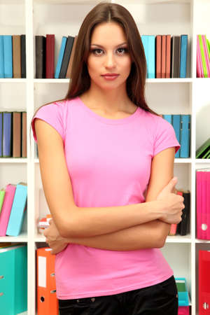 Young attractive female student in library photo