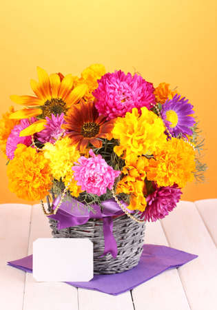 ronantic: Beautiful bouquet of bright flowers with paper note on wooden table on yellow background