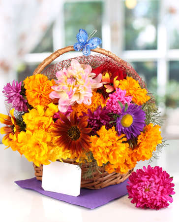 ronantic: Beautiful bouquet of bright flowers in basket with paper note on white table on window background