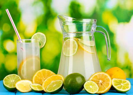 limonada: Citrus limonada en una jarra y un vaso de c�tricos alrededor en la mesa de madera natural sobre fondo azul