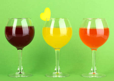 Colorful cocktails on green background photo