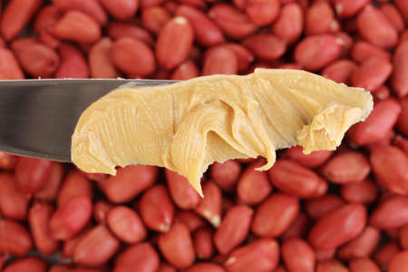 Delicious peanut butter on knife on peanuts background close-up photo
