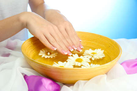 handcare: woman hands with wooden bowl of water with flowers, on blue background Stock Photo
