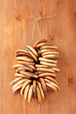 tasty bagels on rope, on wooden background photo