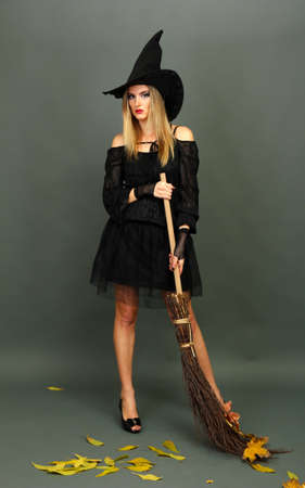 Halloween witch with  broom on gray background photo