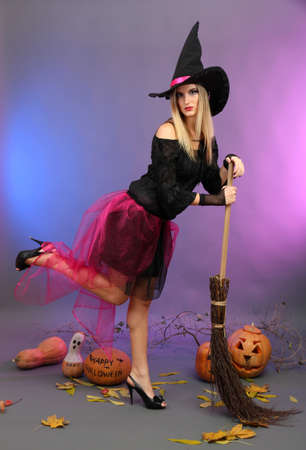 Halloween witch with  broom on color background photo