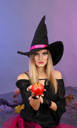 Bruja de Halloween con la manzana roja sobre fondo de color photo