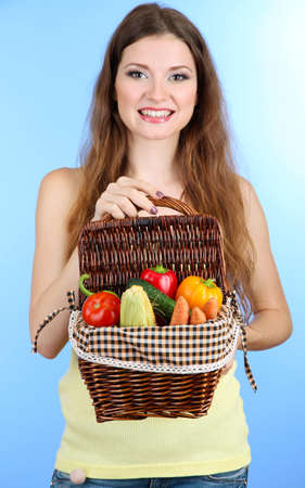Beautiful woman with vegetables in wicker basket on blue background photo