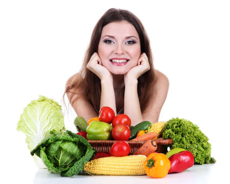 Beautiful woman with vegetables on table isolated on white photo