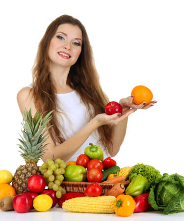 Beautiful woman with vegetables and fruits on table isolated on white photo