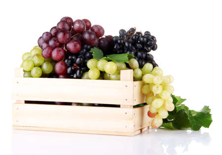 assortment of ripe sweet grapes in wooden crate, isolated on white  photo