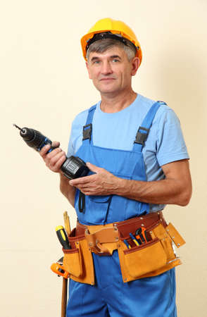 Builder with drill on wall background photo
