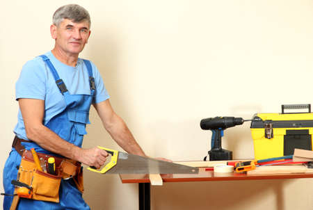 Builder sawing boards on table on wall background photo