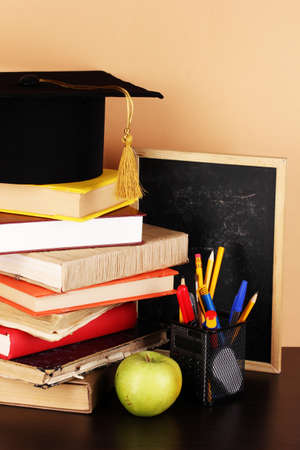 Books and magister cap against school board on wooden table on beige background photo