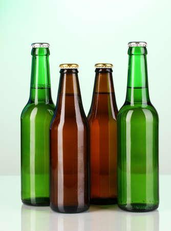 botellas de cerveza: Coloured botellas de cerveza de vidrio sobre fondo verde