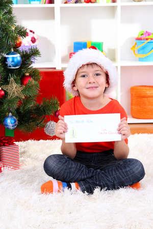 Little boy in Santa hat writes letter to Santa Claus Stock Photo - 17282791