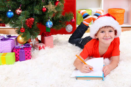 Little boy in Santa hat writes letter to Santa Claus photo
