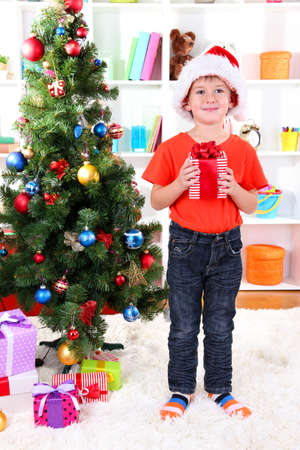 Little boy in Santa hat stands near Christmas tree with gift in his hands photo