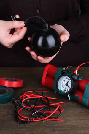 Human makes timebomb on wooden table on black background Stock Photo - 16646901
