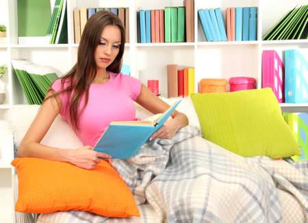 Portrait of female reading book while lying on couch Stock Photo - 17051841