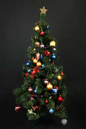 toygift: Decorated Christmas tree isolated on black