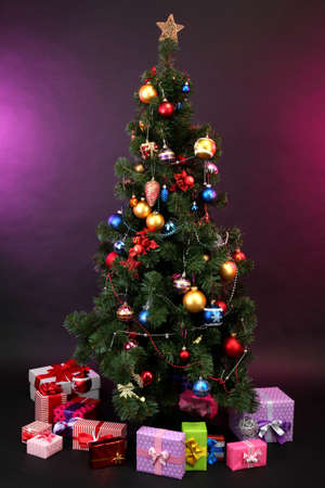 toygift: Decorated Christmas tree with gifts on dark color background Stock Photo