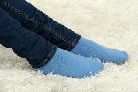 Female legs in colorful socks on  white carpet background photo