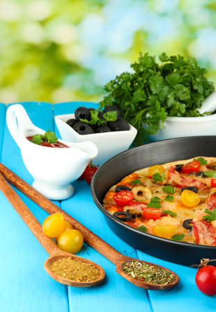 colorful composition of delicious pizza, vegetables and spices on blue wooden background close-up photo